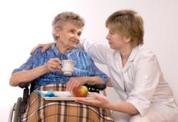 Caregiver serving food to an elder