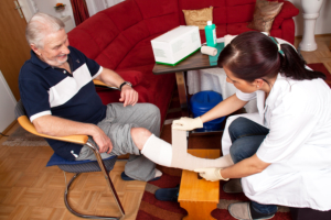 Nurse replacing the wound dressing of a senior