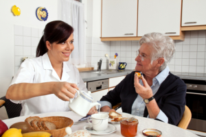 Caregiver pouring a cup of milk for the senior